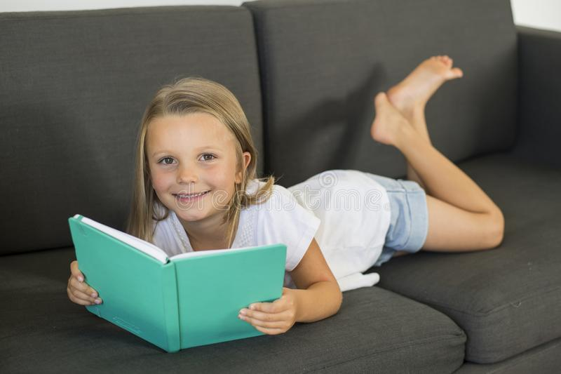 Young sweet and happy little girl 6 or 7 years old lying on home living room sofa couch reading a book quiet and adorable in child royalty free stock photography