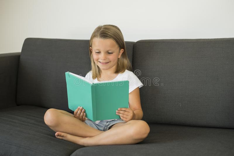 Young sweet and happy little girl 6 or 7 years old sitting on home living room sofa couch reading a book quiet and adorable in chi stock image