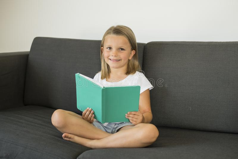 Young sweet and happy little girl 6 or 7 years old sitting on home living room sofa couch reading a book quiet and adorable in chi. Ldren education and lifestyle stock images