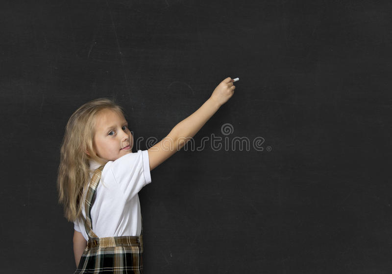 Young sweet junior schoolgirl with blonde hair standing happy and smiling writing with chalk in blackboard stock photo