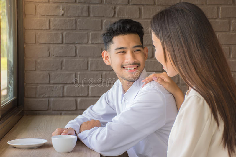 Young sweethearts smiling while sitting at table and drinking coffee at coffee shop/Happiness and healthy relationship concept. stock photography
