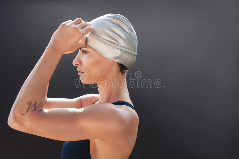 Young swimmer getting ready for a swim. Young sportswoman in swimsuit getting ready for a swim. Sportswoman in swimming costume looking away with copy space on royalty free stock image