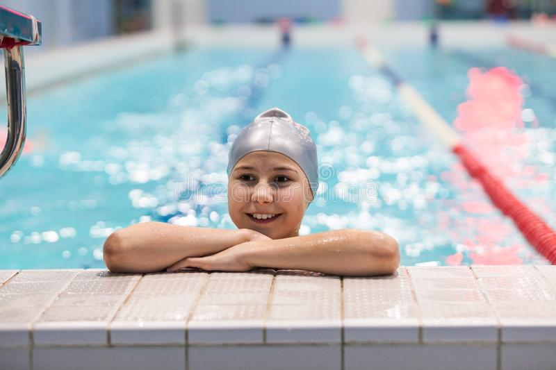 Young swimmer girl. Portrait of ten years old Caucasian athlete in swimming cap in pool stock photography