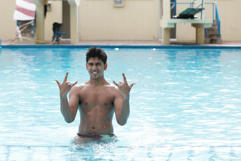 A young swimmer poses in swimming pool stock image