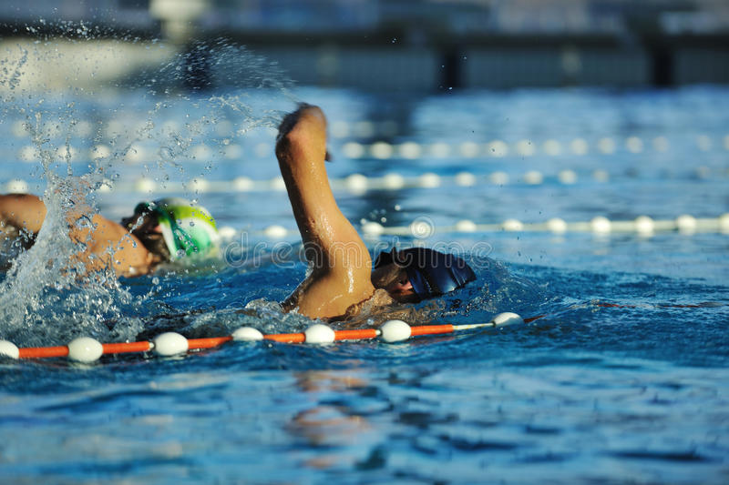 Young swimmmer on swimming start. Start position race concept with fit swimmer on swimming pool stock photo
