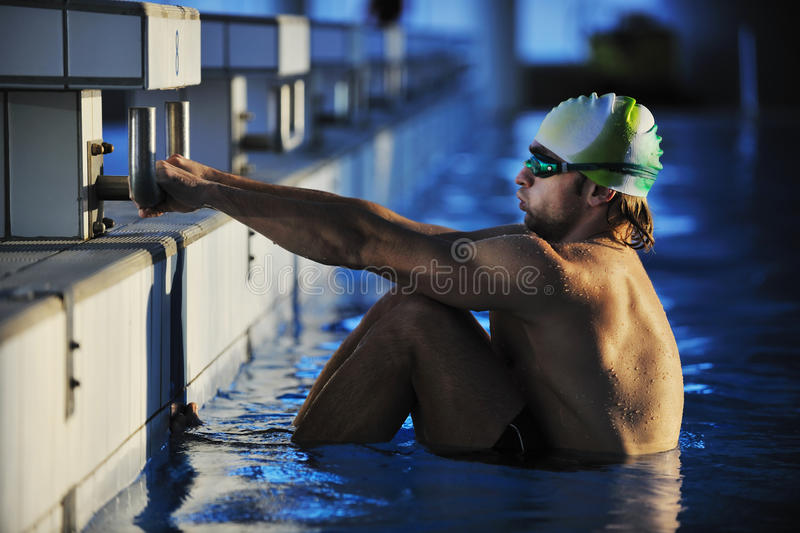 Young swimmmer on swimming start. Start position race concept with fit swimmer on swimming pool stock photography
