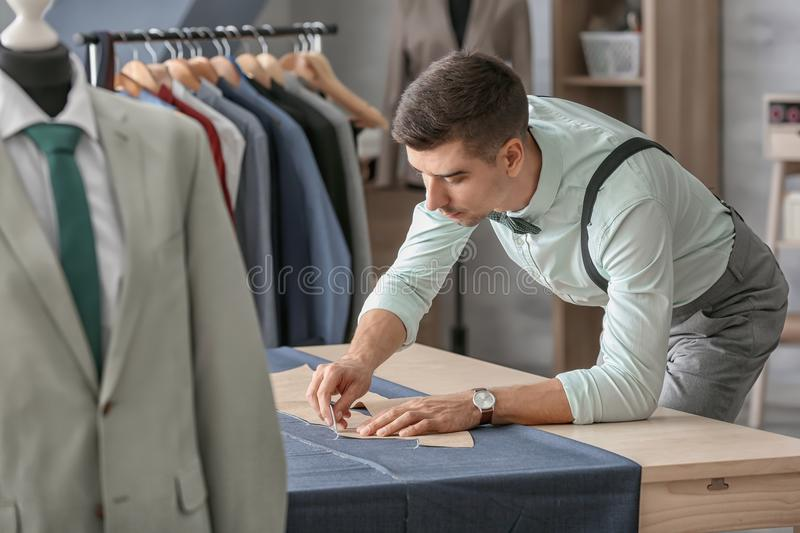 Young tailor working with sewing pattern royalty free stock photography