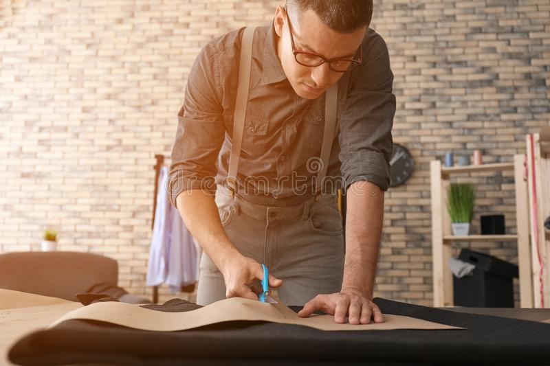 Young tailor working with sewing pattern in atelier royalty free stock photography
