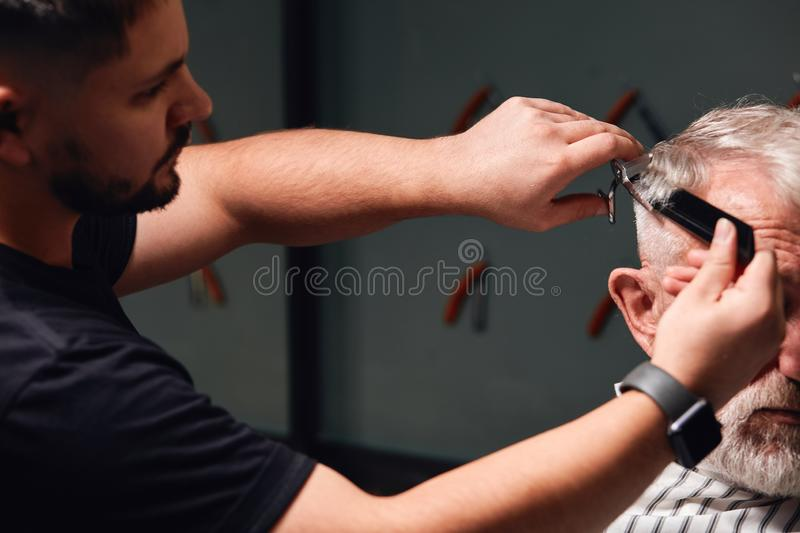 Young talented barber doing new modern hairstyle stock photography