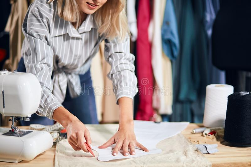 Young talented creative female fashion designer working on her designs in studio royalty free stock photography