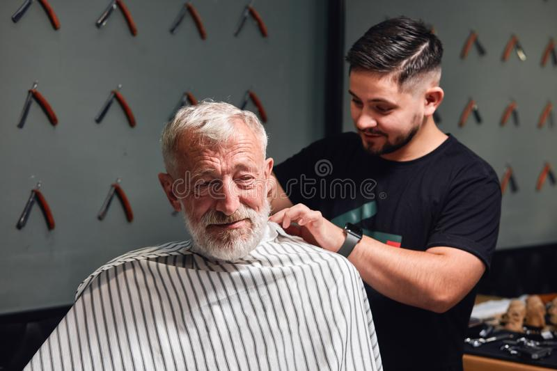 Young talented experienced barber enjoying his work at barbershop royalty free stock photo