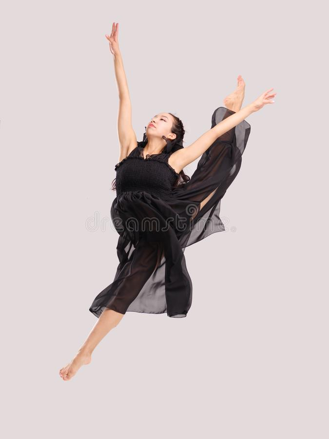 Young and talented gymnast girl jumping up spreading her legs in a twine. stock photography