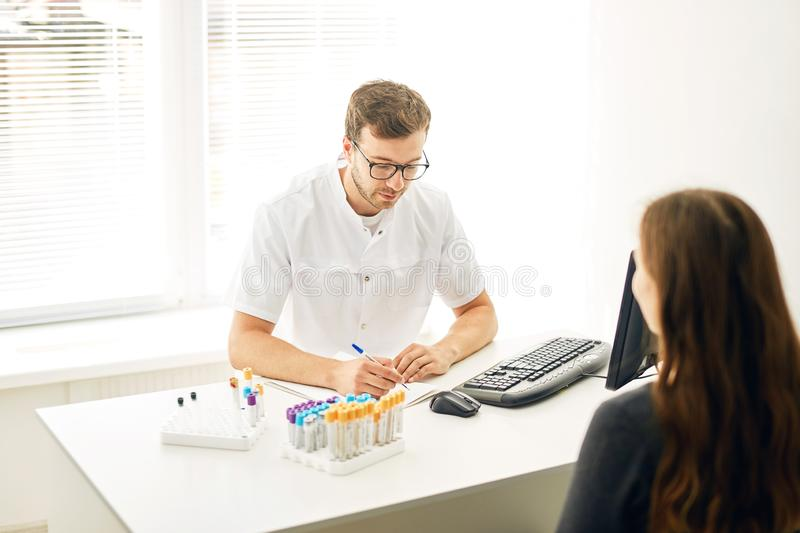 Young talented therapist writing a prescription to a sick woman stock image