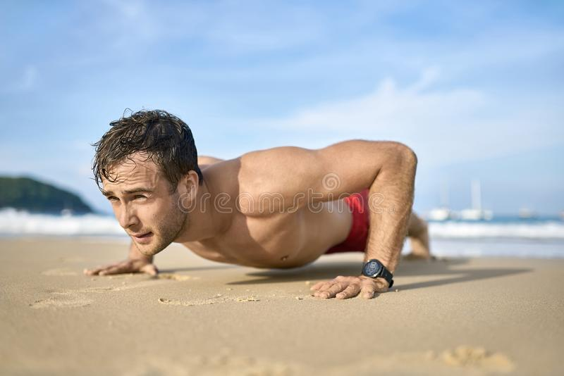 Sportive guy training on beach. Young tanned man does a low plank on the sand beach on the sunny background of the sea with white boats and the blue sky. He stock photography
