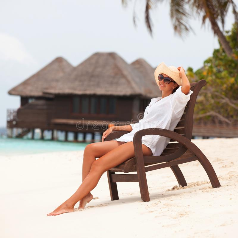 Young tanned woman sit at the chair and relax near bungalow of resort on the beach. Happy woman vacation. Island lifestyle. Rest royalty free stock photos
