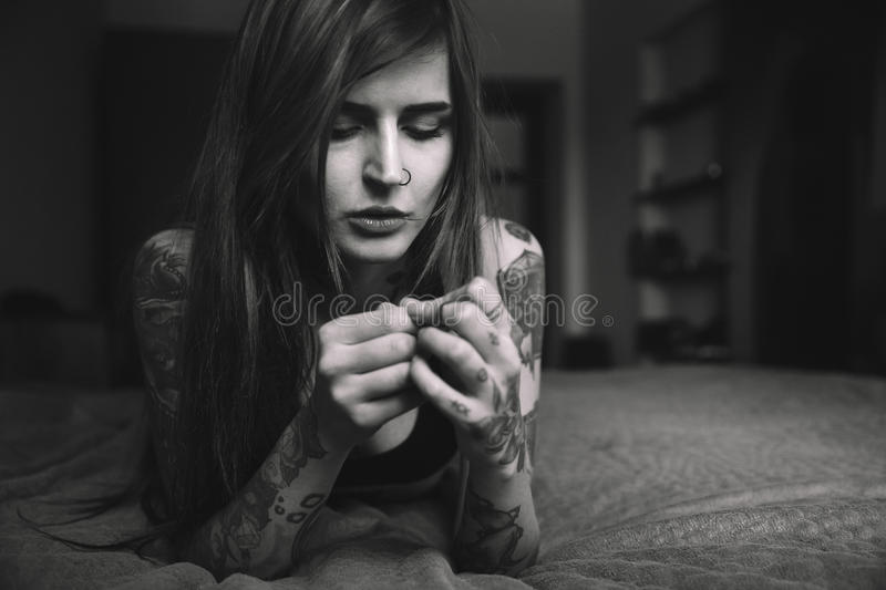 Young tattooed woman with long hair lying on the bed, looking o stock images