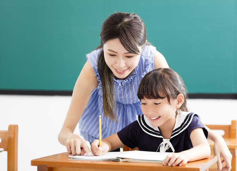 Young Teacher helping child with writing lesson. Asian young Teacher helping child with writing lesson stock photo