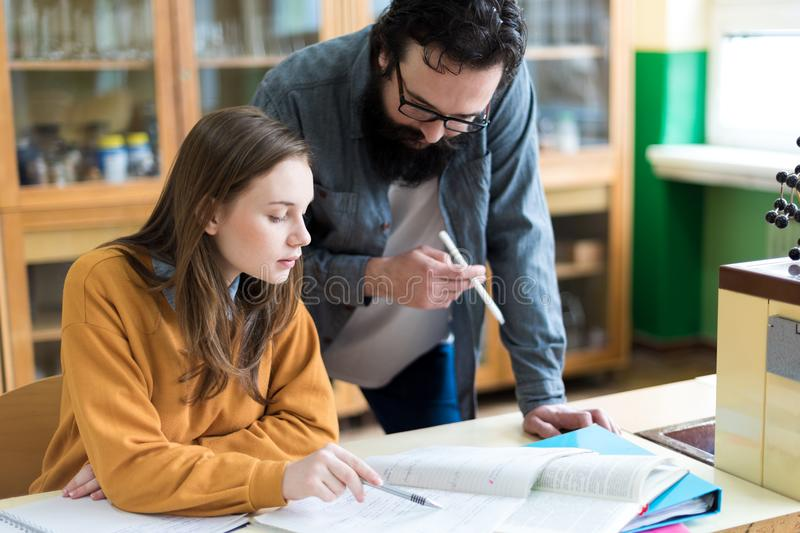 Young teacher helping his student in chemistry class. Education and Tutoring concept. stock photo