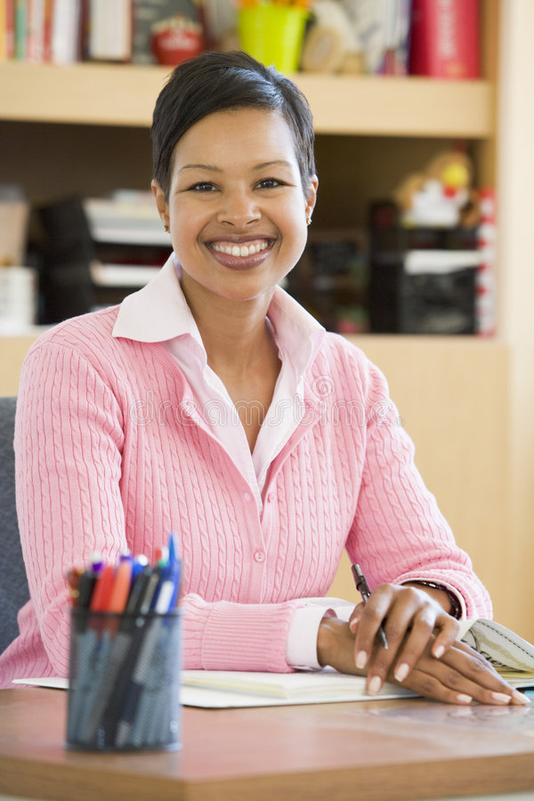 Young Teacher At Her Desk Royalty Free Stock Image