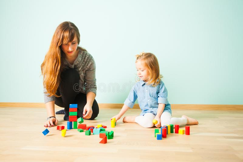 Young teacher sitting on a floor communicating with her pupil. Young female teacher with long dark hair sitting on a floor communicating with girl her pupil stock photo