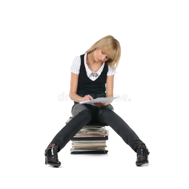 A young teacher is sitting on a sack of books royalty free stock photos
