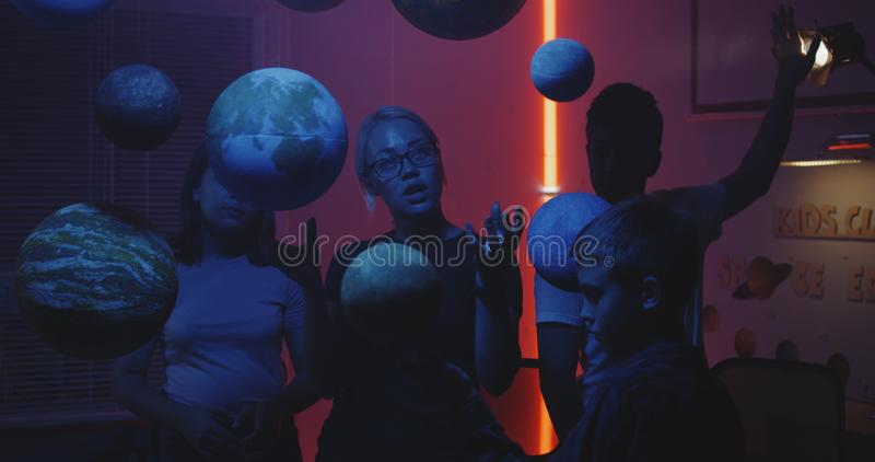 Young teacher teaching astronomy with planet models. Medium shot of a female teacher explaining astronomy to students with suspended planet models royalty free stock images