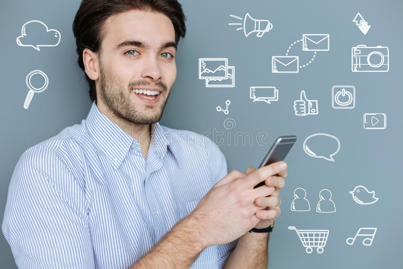 Young teacher typing messages to his students and smiling stock image