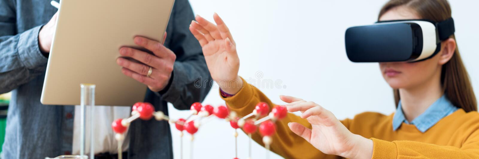 Young teacher using Virtual Reality Glasses and 3D presentation to teach students in chemistry class. Education, VR, Technology. royalty free stock photos