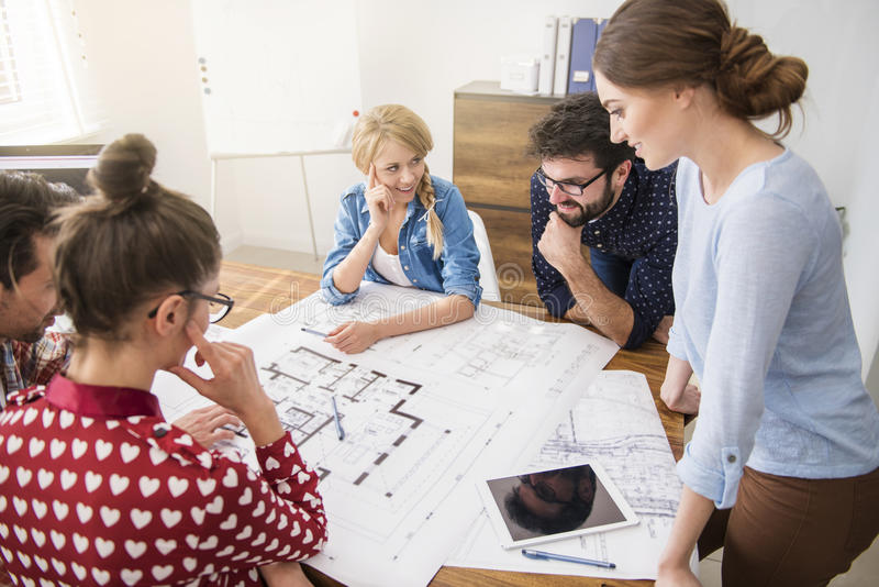Young team of architects. This project isn't as easy as we thought stock photography