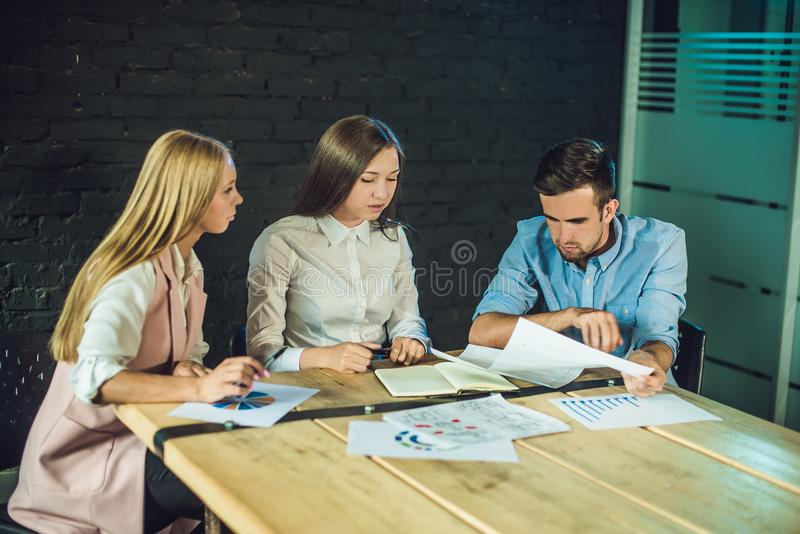 Young team of coworkers watching storyboard for shooting video in modern coworking office. Teamwork process. Horizontal,blurred ba stock photography