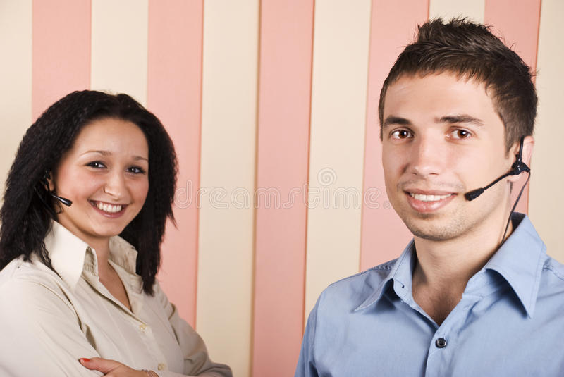 Young team of customer service. Young team with two people,woman and man customer service with headphone smiling and looking you,focus on man.Check also,for royalty free stock photos