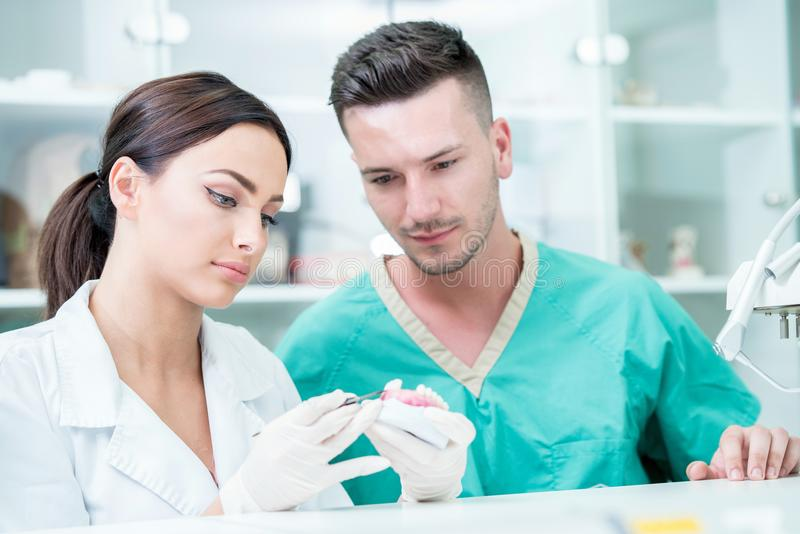 Young team of dental technicians making teeth prostetics. Process of making denture. stock photography