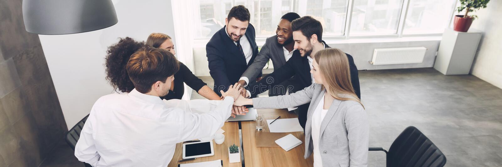 Young team joining hands involved in teambuilding activity stock photo