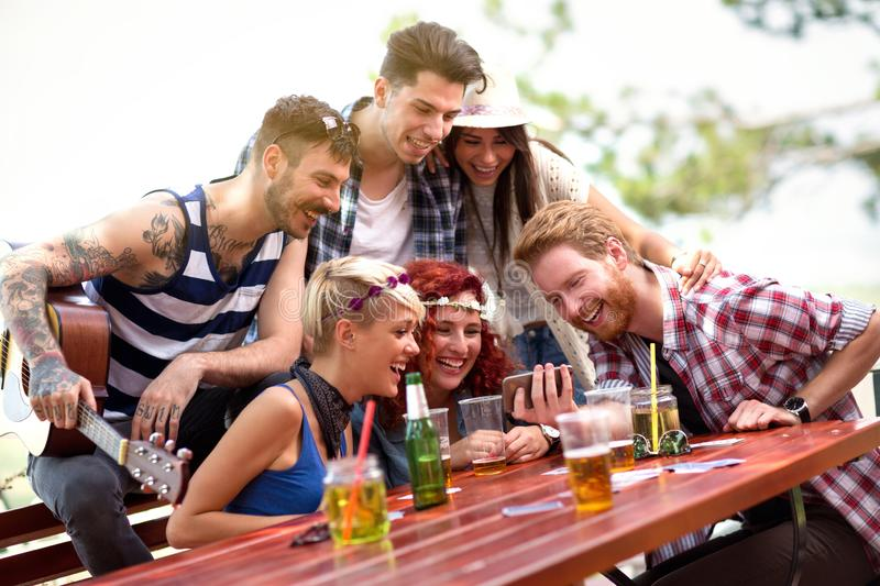 Young team are laughing while watching their photos on mobile phone stock image