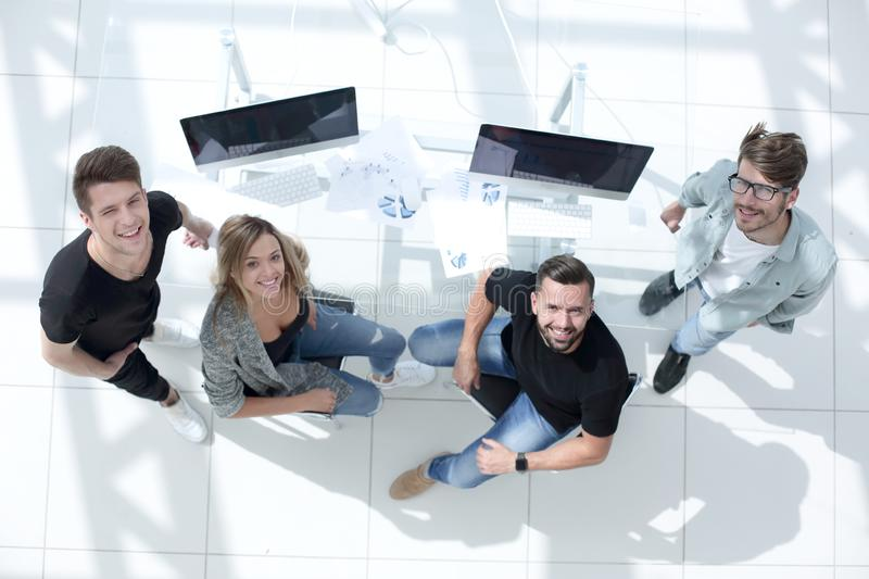 Young team of people sitting at table and looking up royalty free stock photos