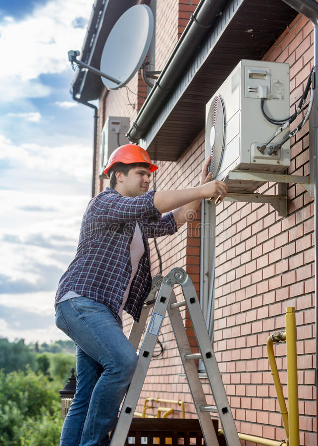Young technician repairing outside air conditioning unit. Portrait of young technician repairing outside air conditioning unit royalty free stock images