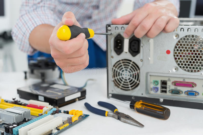 Young technician working on broken computer royalty free stock photography