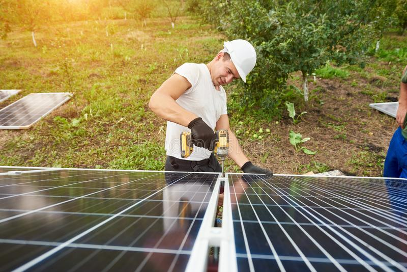 Installation of stand-alone exterior photo voltaic panels system. Renewable green energy generation. Young technician working with screwdriver connecting solar stock image