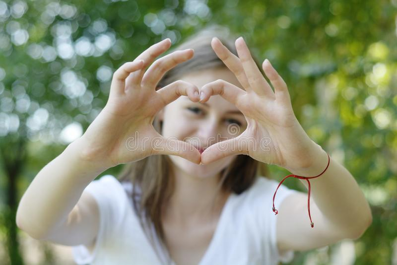 Young teen age girl showing happy heart gesture with hand. Approving expression looking at the camera. Summer, green background. Young teen age girl showing royalty free stock photo