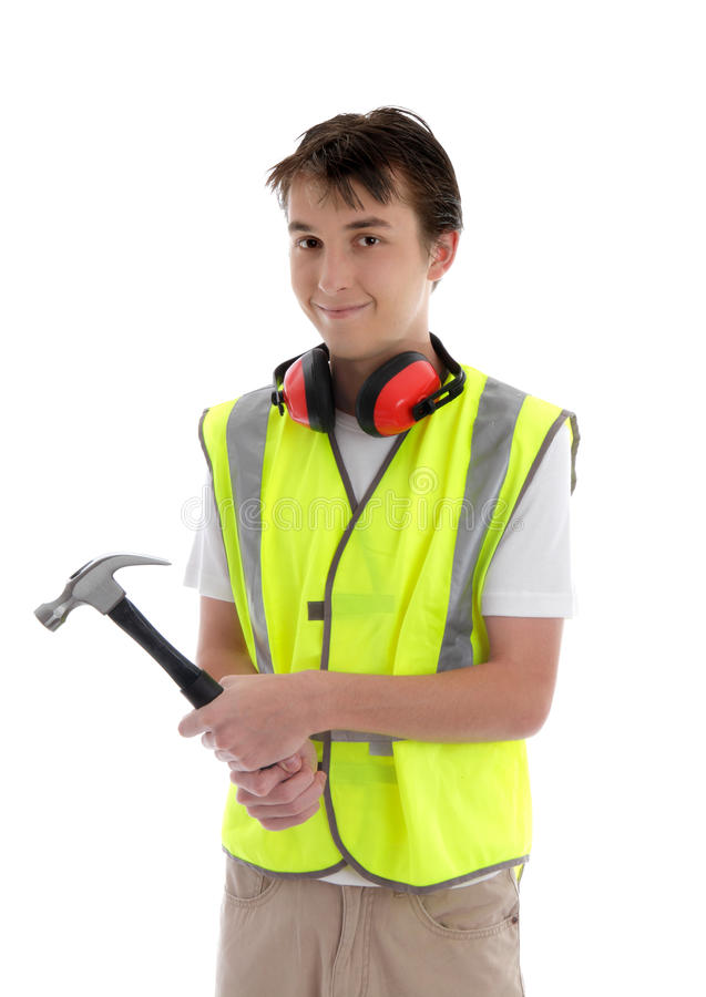 Young teen apprentice builder holding hammer. Teenager holding a hammer and smiling. White background royalty free stock photo