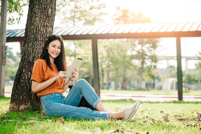 A young or teen asian girl student in university smiling and reading the book and look at the tablet royalty free stock photo