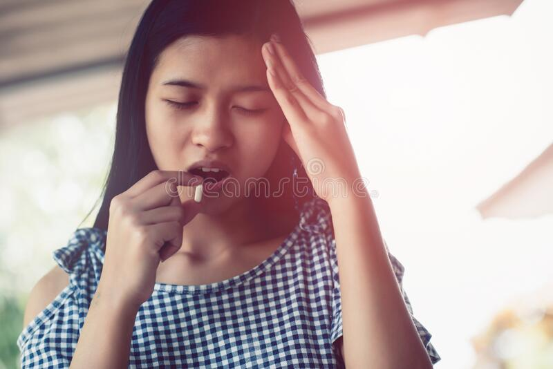 Young teen asian woman headache holding medicine and her head royalty free stock images