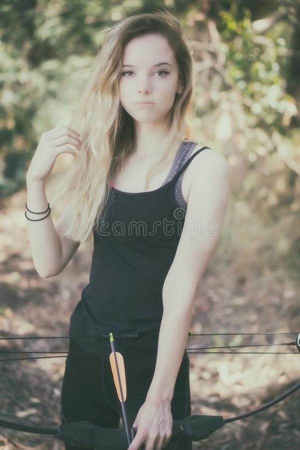 Teen girl with bow and arrow royalty free stock photo