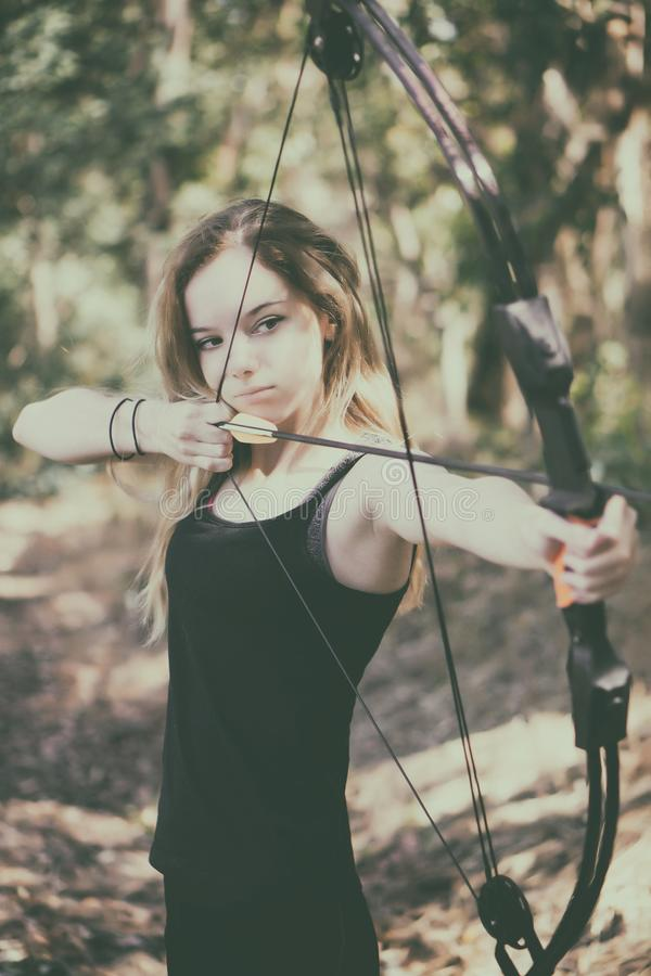 Teen girl with bow and arrow stock photo