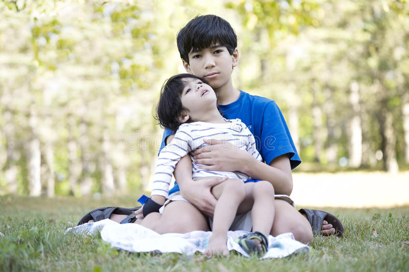 Young teen boy caring for disabled brother stock photo