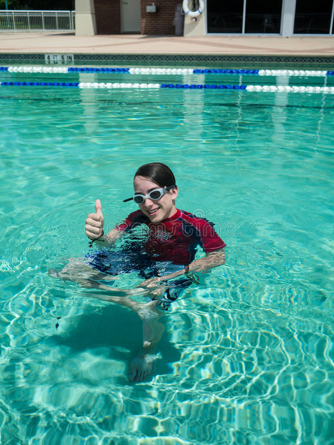Young teen boy giving thumbs up in the pool royalty free stock photography