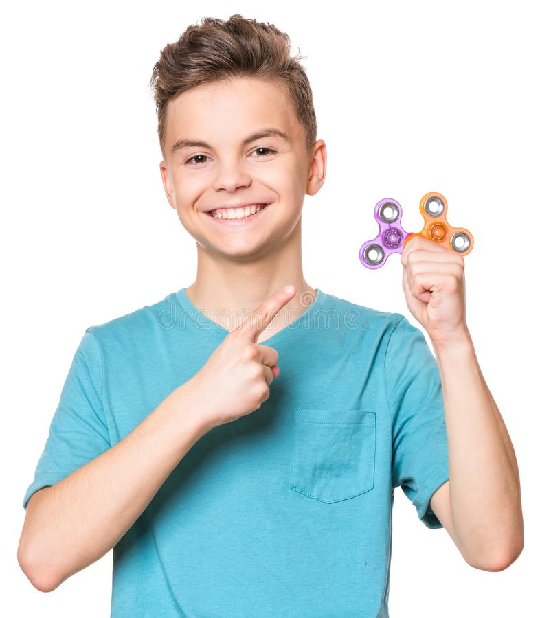 Teen boy with spinner toy. Young teen boy holding popular fidget spinner toy - close up portrait. Happy smiling child playing with Spinner, isolated on white royalty free stock photo