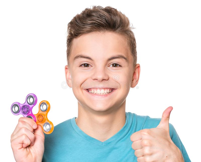 Teen boy with spinner toy. Young teen boy holding popular fidget spinner toy and making thumb gesture. Happy smiling child playing with Spinner, isolated on royalty free stock images
