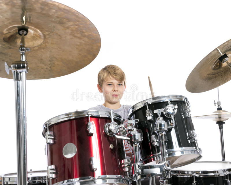 young teen boy plays the drums in studio against white background stock image