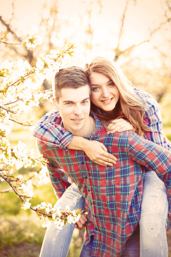 Young teen couple in the spring blossom apple trees stock photos